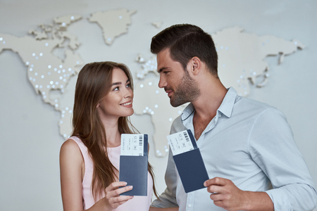 Portrait of joyful glad couple holding passport with flying tickets in hands pointing with forefinger looking to each other on map background 写真素材