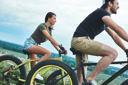Couple riding bicycles one after another