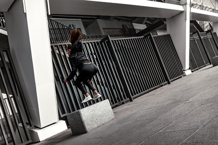 Young woman doing leg exercises with stoned step platform