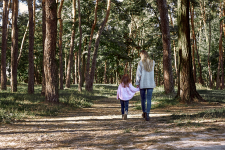 Happy little girl is walking with her beautiful mother in forest, rear view