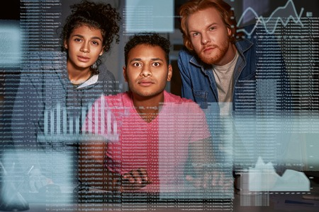Young team of data analysts are captivated by the code Stock Photo