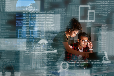 Young indian developer and his project manager discussing application code Stock Photo