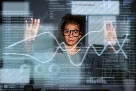 La femme indienne regarde jeter les graphiques dans les écrans numériques Banque d'images