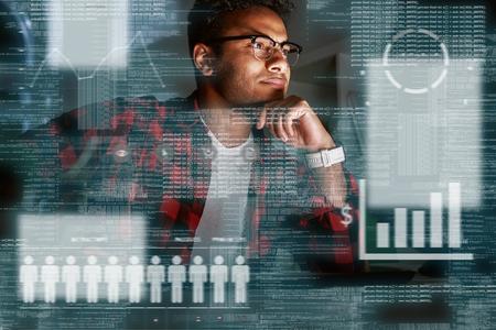 Especialista en SEO indio concentrado joven mirando por encima de la conversión de publicidad Foto de archivo