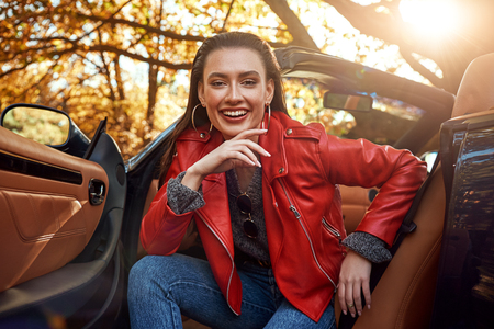 Woman in red in cabriolet. She is smiling and looking to the camera