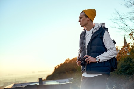 Young tourist blogger in hat meets sunrise Reklamní fotografie