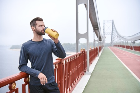 Tired after jogging. Young manin sports clothing bending and looking tired while standing on the bridge and urban view i