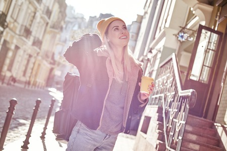 Young attractive tourist woman is drinking coffee on the street