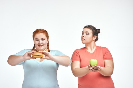Chubby women: one woman is holding a sandwich,another one holding an apple Imagens