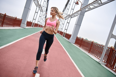 Morning workout. Full length rear view of young womanin sports clothing exercising while jogging on the bridge outdoors Stock fotó