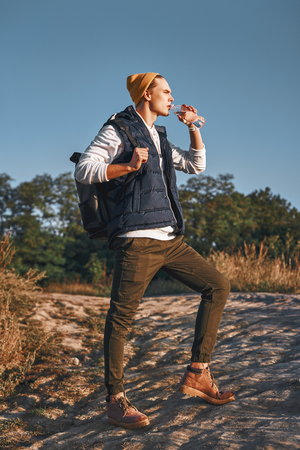 Young stylish tourist blogger is drinking water while walking at the mountains Stock fotó