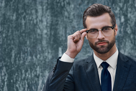 Young businessman looking into the distance holding one-handed glasses
