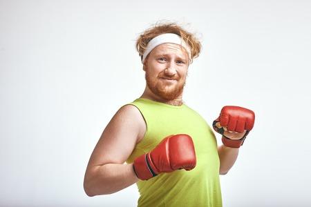 Homme aux cheveux rouges, barbu et dodu portant des vêtements de sport et des gants de boxe rouges