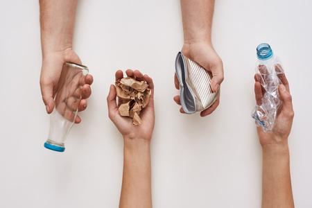 Risparmia la tua spazzatura. Quattro tipi di immondizia nelle mani dell'uomo Archivio Fotografico