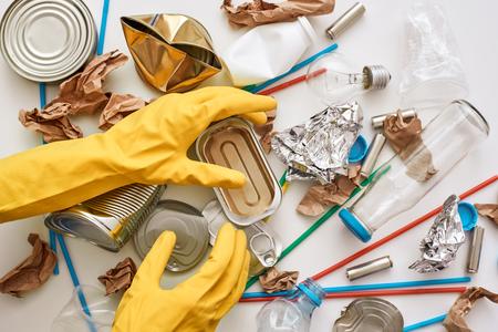 Clean the world. Hands in orange gloves under the trash Imagens