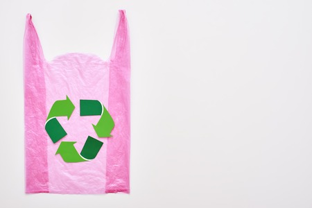 Live green. Isolated recycle symbol at pink plastic bag