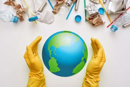 Protect the worlds ecology. Different types of garbage attacked the globe Stock Photo