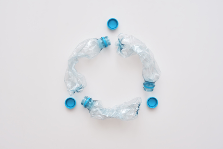 Step to green life. Circle of crumple plastic bottles