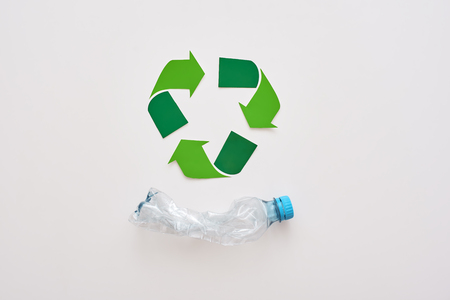 Think about ecology. Isolated recycle symbol and crumple plastic bottle