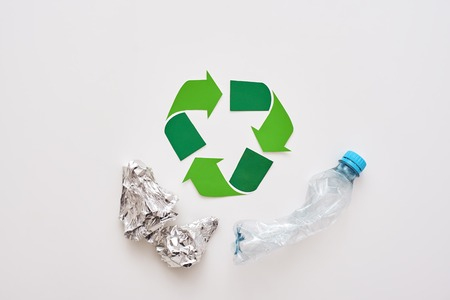 Foil and plastic. Crumple foil and plastic are lying near recycle symbol