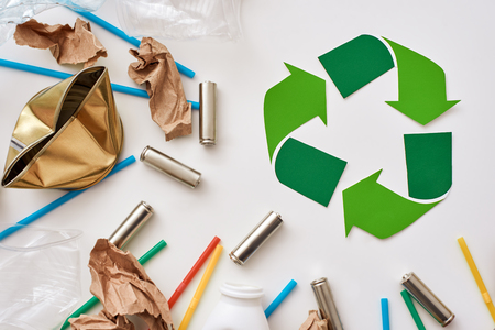 Think about ecology. Crumple paper, plastic and batteries near recycle symbol