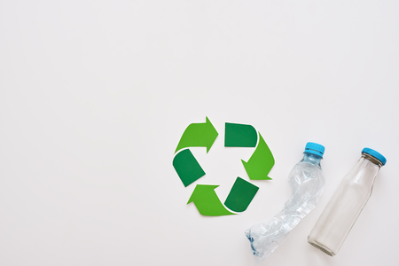 Think about ecology. Isolated recycle symbol and crumple plastic bottles
