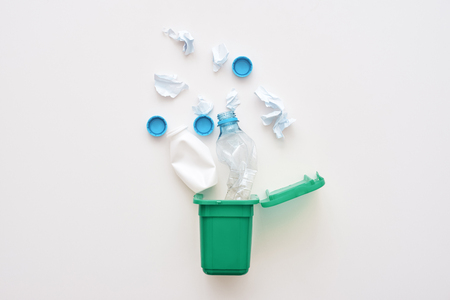 Plastic garbage from milk and water are falling into recycled bin, isolated Reklamní fotografie