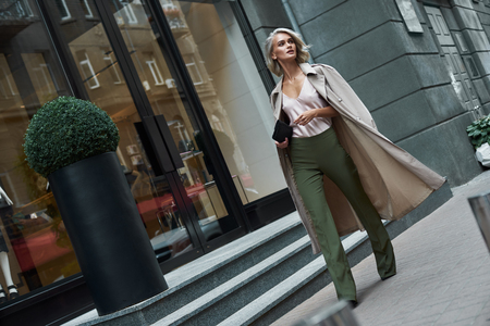 Fashion. Young stylish woman walking on the city street looking aside curious Stock Photo