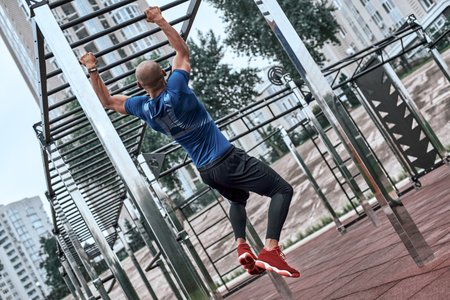 An african man is exercising at open air gym