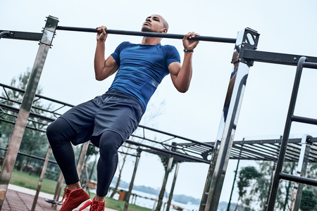 An african man is pulling up at open air gym