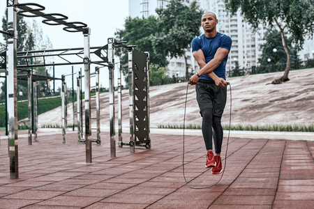 Muscular black man skipping rope. Portrait of muscular young man exercising with jumping rope on national park background
