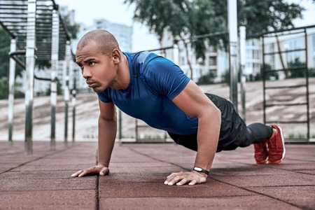 African man is doing plank at open air gym near the park Banco de Imagens