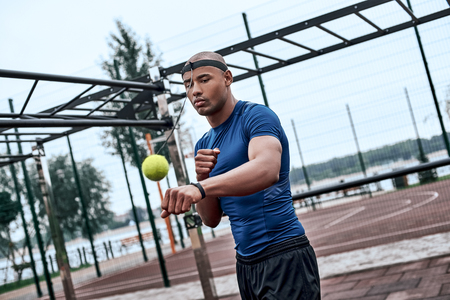 An african man is boxing with tennis ball at open air gym