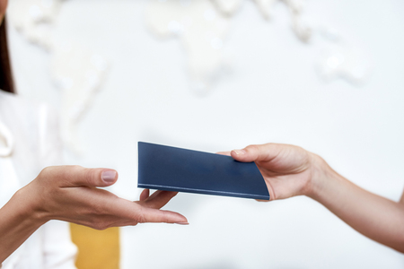 Female hand giving passport with visa to client.Travel concept. Stock Photo