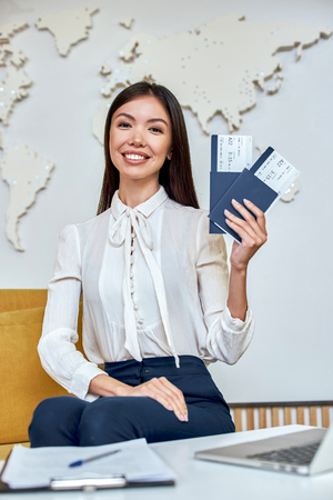 Young woman travel agent with flight tickets in hands Archivio Fotografico - 114022478