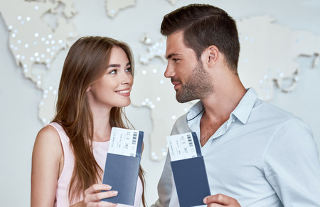 Joyful couple looking to each other and holding passport with flying tickets