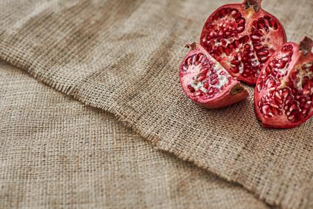 Autumn vitamins. Read juicy pomegranate sliced at sackcloth