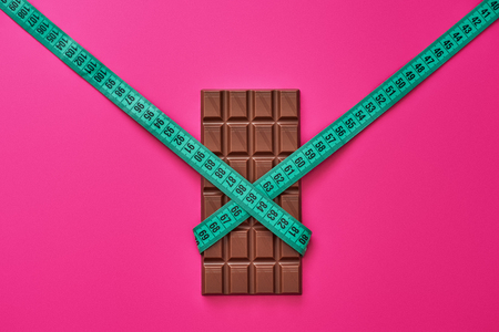 Chocolate bar wrapped with measure tape isolated on pink background