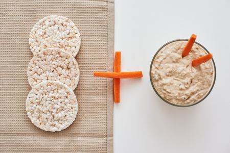 Hummus with carrot sticks. Top view oh humus with carrot isolated on white background.