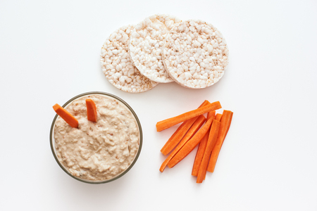 Hummus with carrot sticks. Top view of humus with carrot isolated on white background. Standard-Bild