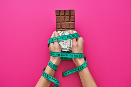 Chocolate bar in womans hands wrapped with measure tape isolated on pink background Stock Photo