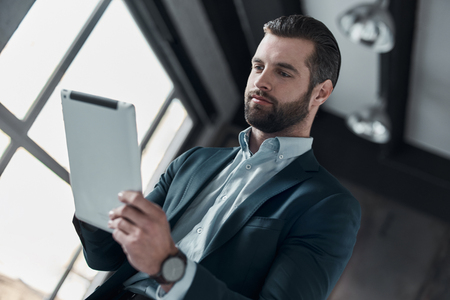 Young stylish businessman leader indoors at office using digital
