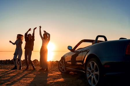 Cheerful young three women are dancing near cabriolet Zdjęcie Seryjne