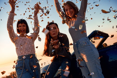 Cheerful young three women are dancing near cabriolet