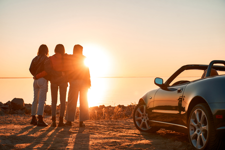 Cheerful young three women standing near cabriolet wathing at sunset