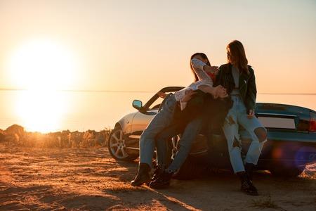 Cheerful young three women standing near cabriolet Zdjęcie Seryjne