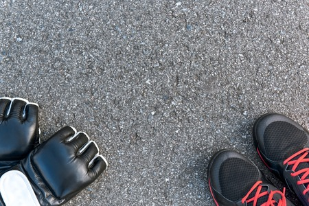 Boxing sports items. Cropped photo of boxing gloves and sportive shoes
