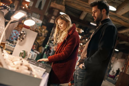 Happy young couple choosing handmade imitation jewelry at small street market Reklamní fotografie
