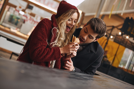 Close-up of young couple are eating sandwiches at the street food market.