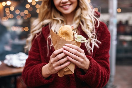 Close-up of young blonde woman eating out sandwich at sandwich bar